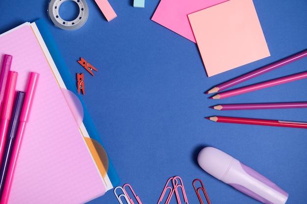 Ассортимент школьных офисных принадлежностей в розовых тонах, изолированных на синем фоне, копирует пространство. тетрадь, фломастеры, маркеры, канцелярские скрепки, карандаши и канцелярские принадлежности, разбросанные по кругу