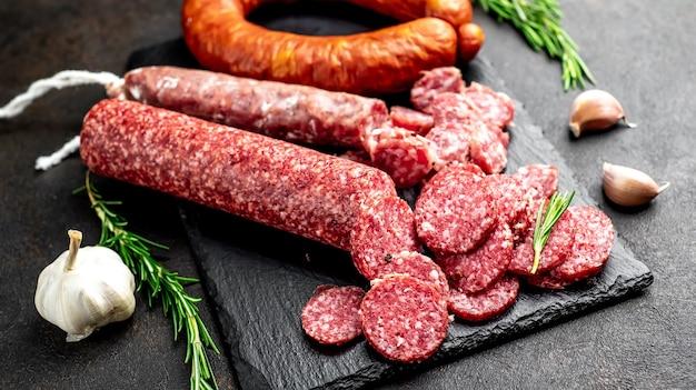 Ассортимент копченых колбас и колбас с плесенью на каменном столе.