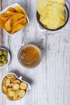 ポテトチップス、ビール、クラッカー、木製のテーブルにグリーンオリーブとブラックオリーブを添えた自宅でのスナックの品揃え