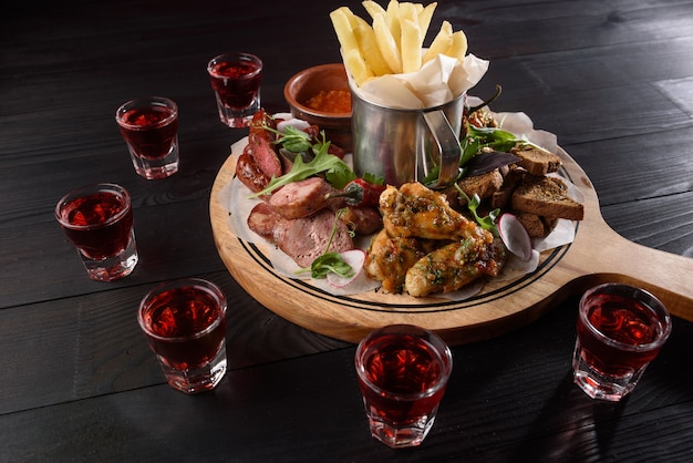 Ассортимент закусок из колбас, куриных крылышек, картофеля фри, гренок, соуса на деревянной тарелке на темном деревянном столе. красный алкоголь в стопках вокруг тарелки с закусками.