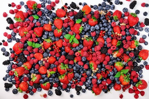 いちご、ブルーベリー、スグリ、ミントの葉の盛り合わせ。夏の果実の背景。フードフレームとボーダーデザイン。ビーガン、ベジタリアンのコンセプトです。