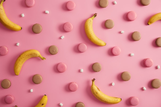 Ассортимент сладких вкусных красочных французских миндальных печений, белого зефира и бананов на розовом фоне. нездоровое высококалорийное печенье и полезные тропические фрукты. идея для вашего десерта