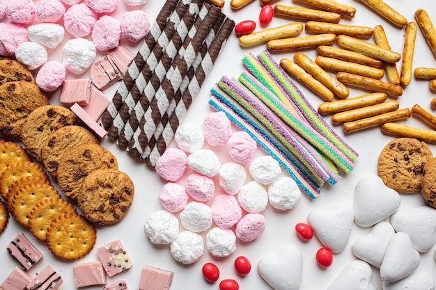 白い背景の上のお菓子の品揃え。様々なお菓子、クッキー、チョコレート、マシュマロ、上面図。