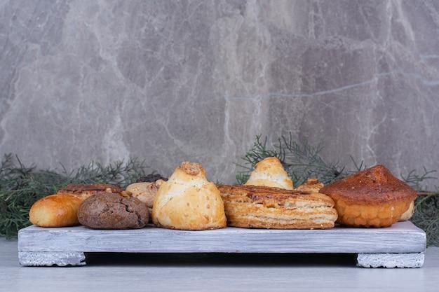 Ассортимент вкусного печенья на деревянной доске.