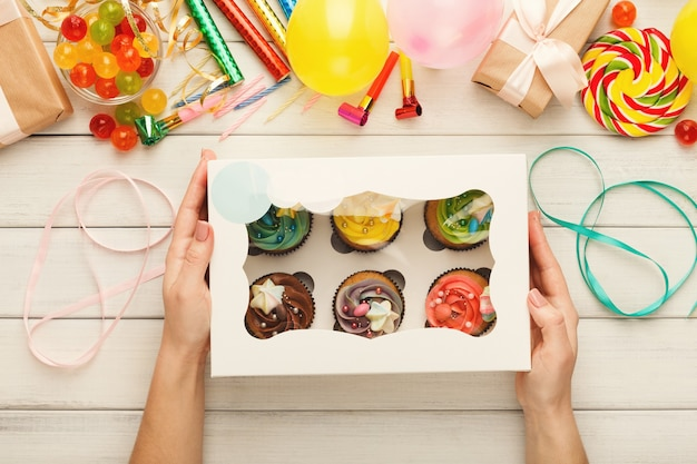 Ассортимент вкусных кексов с разноцветными сливочными топиками в женских руках