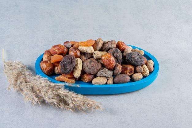 Ассортимент вкусных сухофруктов и орехов на каменном фоне.