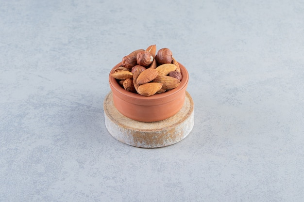 Ассортимент вкусных органических орехов в миске на каменном фоне.