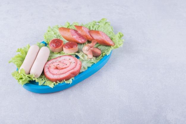 Ассортимент вкусных колбас на синей тарелке.
