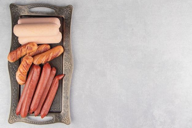 Ассортимент вкусных колбас на металлическом подносе.