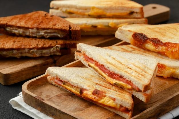 木の板にトーストした三角形のサンドイッチの品揃え