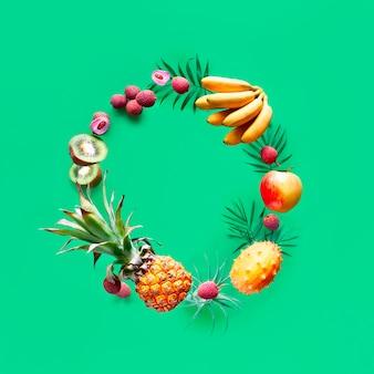緑のテーブルでサークルを飛んでいるトロピカルフルーツの品揃え。パイナップル、キワノ、キウイ、リチー、バナナ-エキゾチックなフルーツの浮揚。
