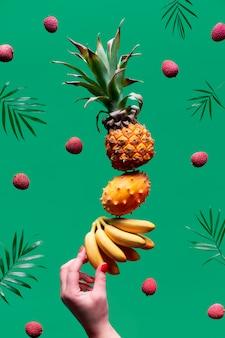 トロピカルフルーツの盛り合わせ、緑の壁に人間の手のバランスをとるピラミッド。パイナップル、キワノ、キウイ、リチー、バナナ-エキゾチックなフルーツで作られたタワー。