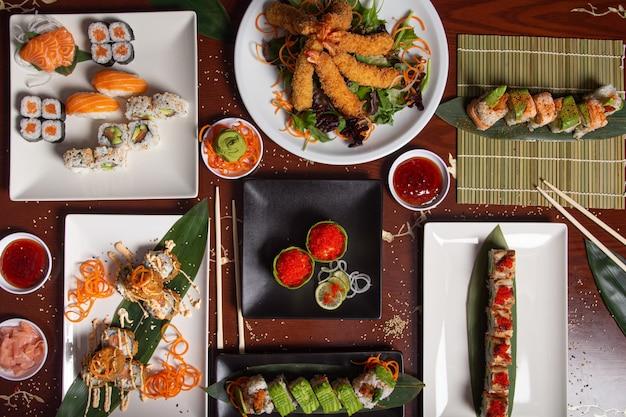 レストランのテーブルで提供される典型的な日本料理の品揃え。寿司、にぎり、天ぷら、巻き。