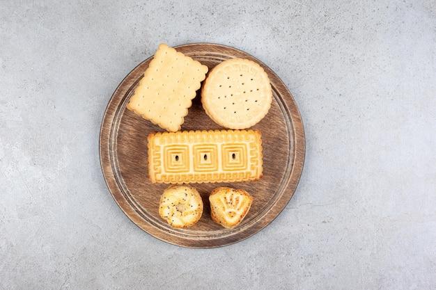Ассортимент различного печенья на деревянной доске на мраморном фоне. фото высокого качества