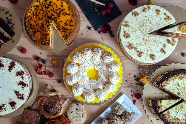 Ассортимент различных тортов свежие из мастерской на деревянный стол. ассортимент тортов для особых торжеств