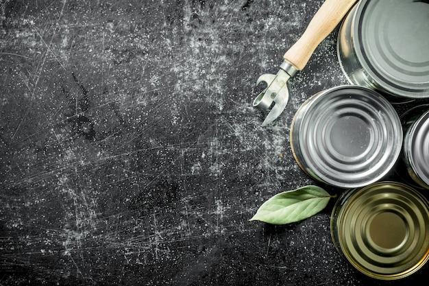 缶切りと月桂樹の葉を使ったさまざまな缶の品揃え。暗い素朴な背景に
