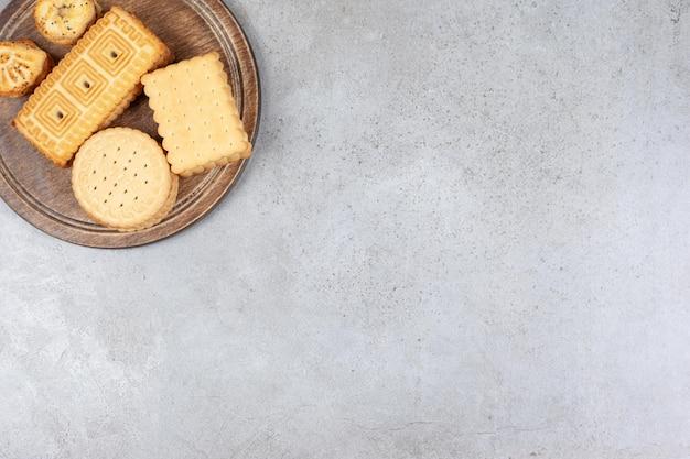 Ассортимент различных восхитительных печений на деревянной доске на мраморном фоне. фото высокого качества