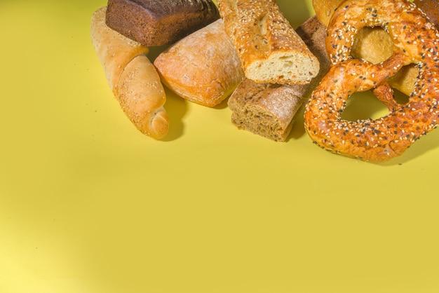 Ассортимент разнообразного вкусного свежеиспеченного хлеба, на модной яркой поверхности, вид сверху, копировальное пространство, узор на желтом