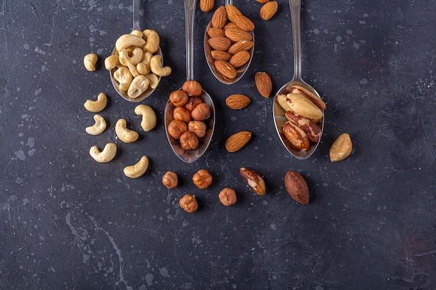 Ассортимент различных видов орехов: кешью, фундук, миндаль, бразильские орехи на металлических серебряных ложках на темном фоне.