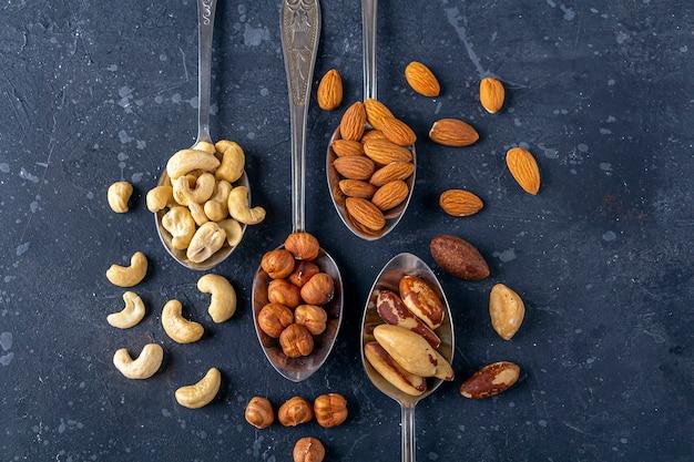 金属製の銀のスプーンにカシューナッツ、ヘーゼルナッツ、アーモンド、ブラジルナッツのさまざまな種類のナッツの品揃え
