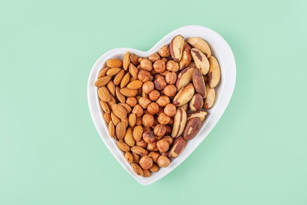 さまざまな種類のナッツの品揃え-緑の背景にハート型のプレートのヘーゼルナッツ、アーモンド、ピーカンナッツ。