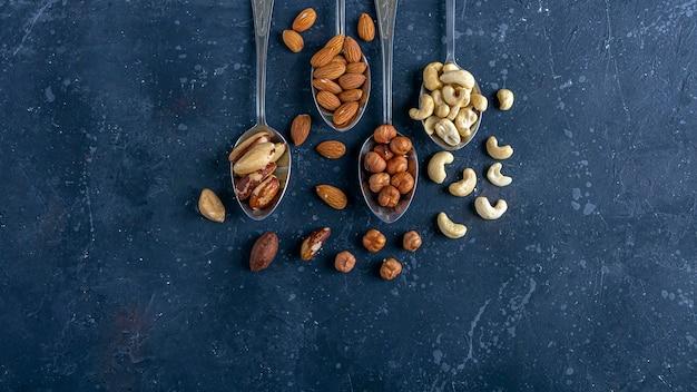 紺色の背景のスプーンにさまざまな種類のナッツの品揃え