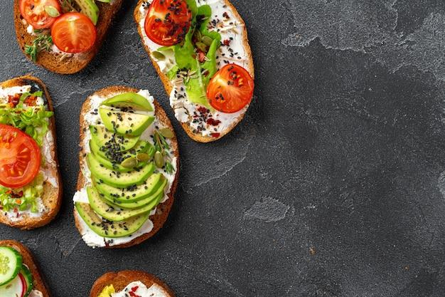 Ассортимент веганских бутербродов с авокадо и помидорами, вид сверху