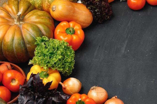 カボチャ、トマト、ピーマンなどの野菜の品揃えと黒地に緑