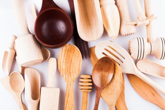 Ассортимент деревянной кухонной утвари на белом фоне