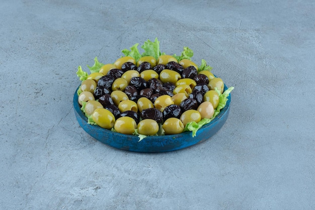Assortimento di olive su un piatto ricoperto di lattuga su una superficie di marmo
