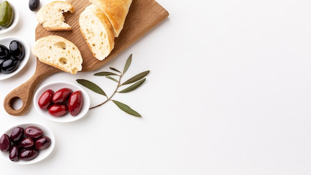 Assortment of olives with bread slices with copy space