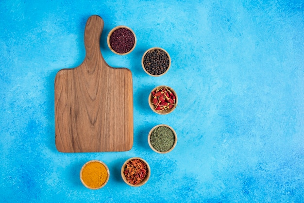 Assortment of organic spices around wooden board.