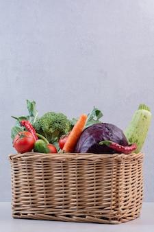 Assortment of organic vegetables in wooden basket.