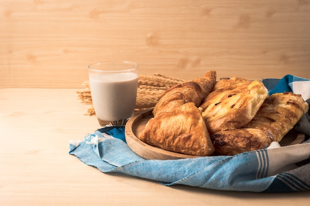 Assortment of pastries with milk on wooden table background.