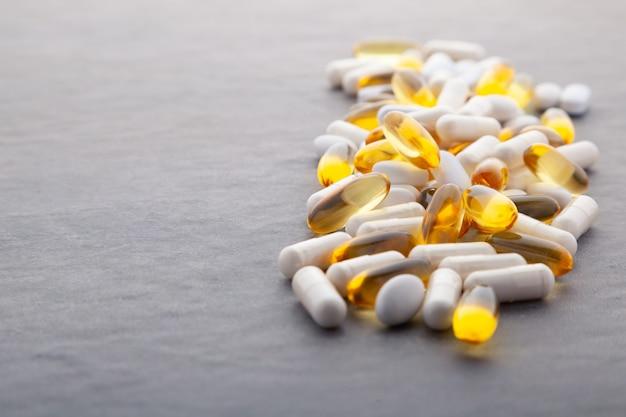Assortment of pharmaceutical medicine vitamins, pills, softgel on gray background