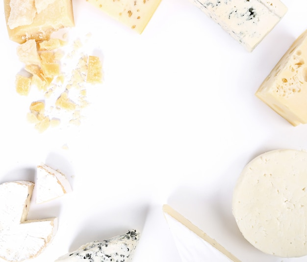 Assortment of pieces of cheese, top view, white copyspace background