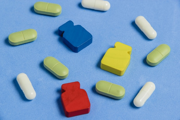 Assortment of pills, tablets and capsules on blue table.