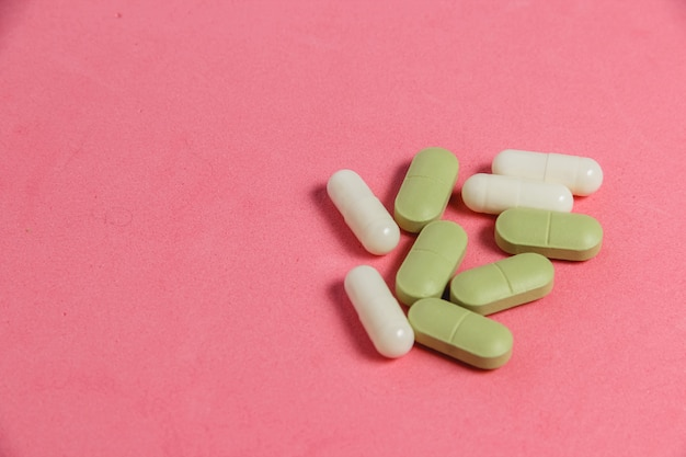 Assortment of pills, tablets and capsules on pink table.