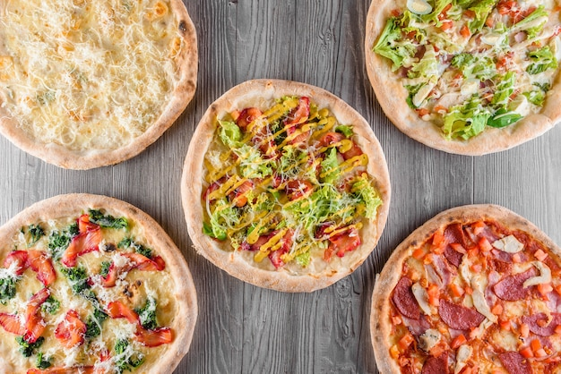 Assortment of pizza with meat, salami, prosciutto, tomatoes, dorblu cheese, mozzarella, parmesan, salad, spinach, red fish on wooden boards. four cheese pizza, caesar, top view.