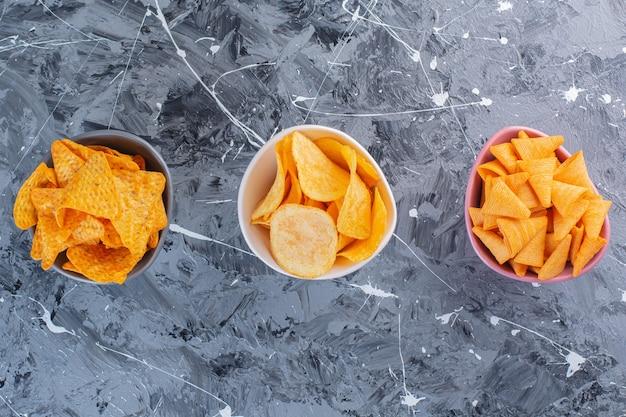 대리석 표면에 그릇에 감자 칩 구색 무료 사진