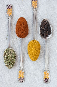 Assortment of powder spices on spoons on a light surface
