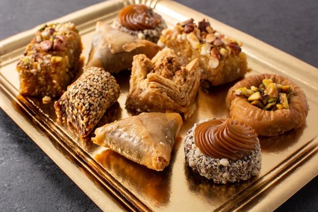 Assortment of ramadan dessert baklava on black slate table