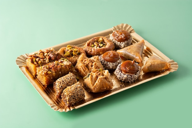 Assortment of ramadan dessert baklava on green table