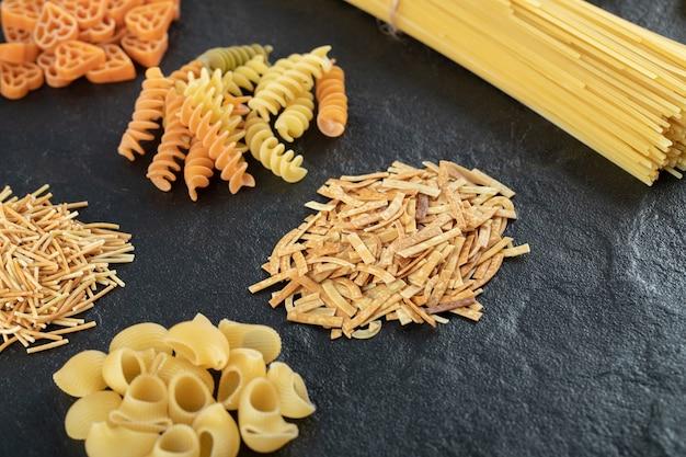 Assortment of raw pasta on dark.
