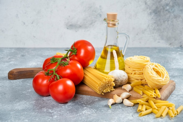 Assortment of raw pasta, olive oil and tomatoes on wooden board.