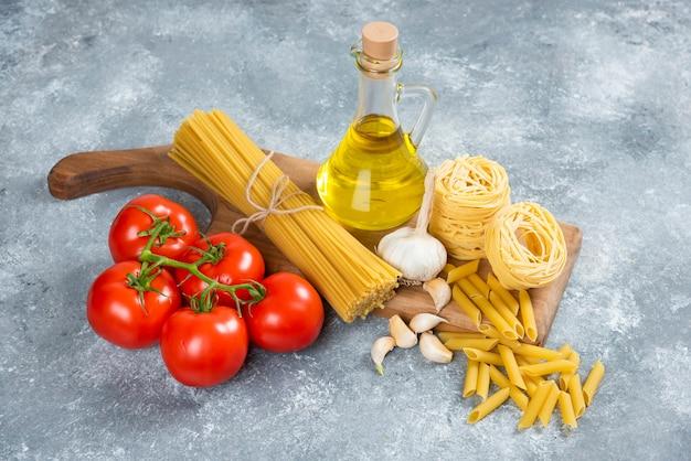 Assortimento di pasta cruda, olio d'oliva e pomodori su tavola di legno.
