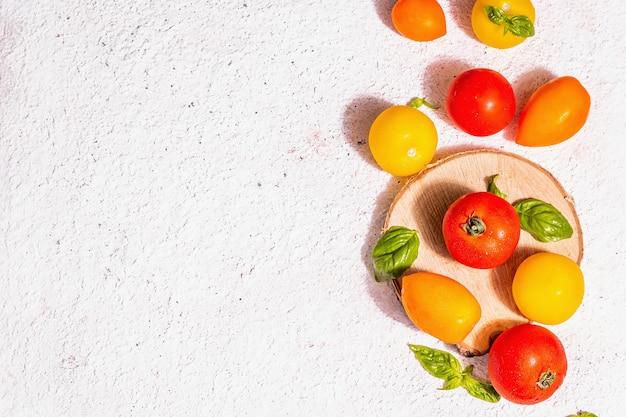 Ассорти из спелых помидоров со свежими листьями базилика. новый урожай, овощи целиком и пополам, модный жесткий свет, темные тени. белый фон шпатлевки, вид сверху
