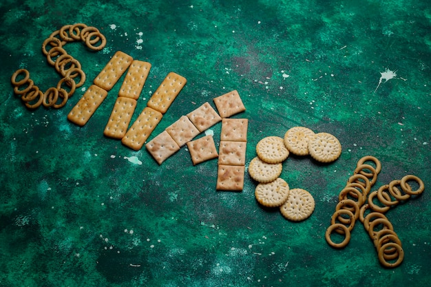 Assortment of salt crackers shot from the top on colorful with copy . salty party snacks mix