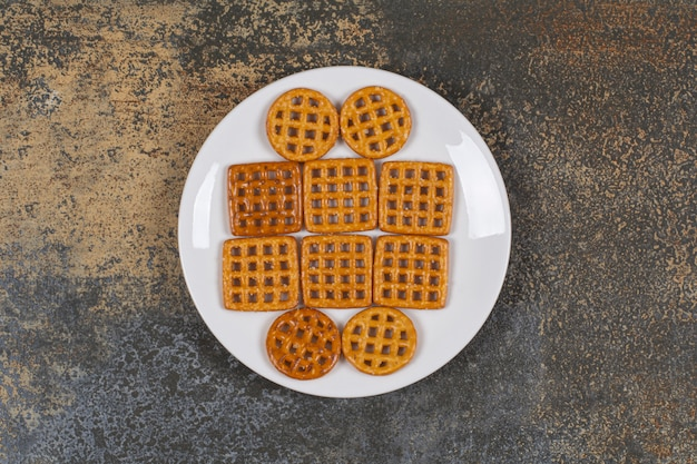 Assortment of salted crackers on white plate.
