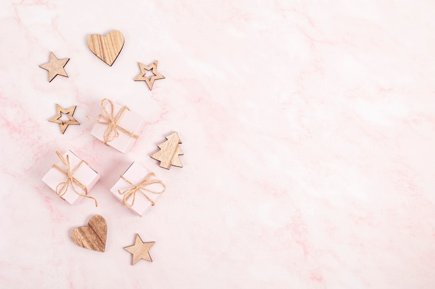 Assortment of scandinavian style, eco friendly, handmade christmas decorations and presents on pink marble background, flat lay, top view with copy space